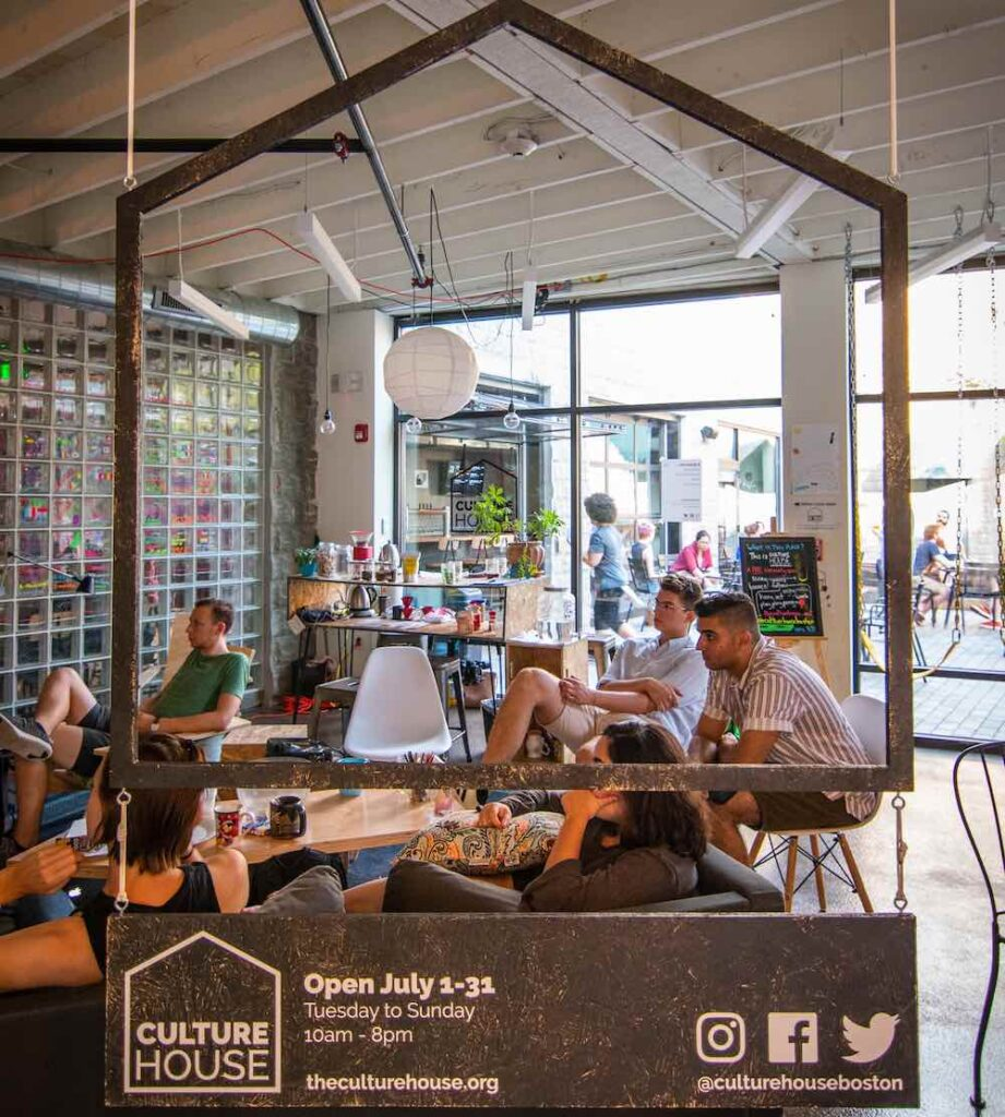 View of people watching a movie at the CultureHouse pop-up in Bow Market through a wooden cut-out of the CultureHouse logo