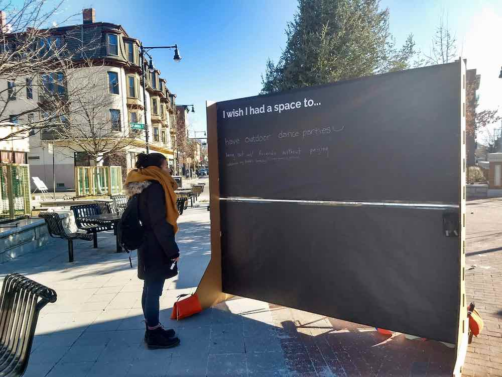 "A woman looks at a large chalk board that reads ""I with I had a place to..."" in Lafayette Plaza in Cambridge"