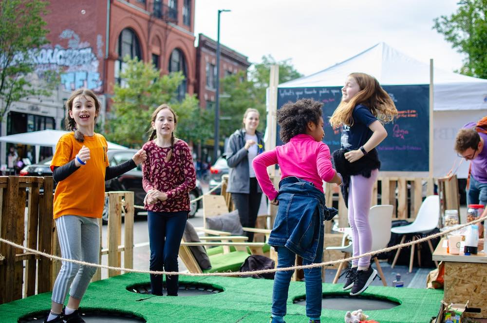 A group of kids jump on trampolines in Central Square during PARK(ing) Day