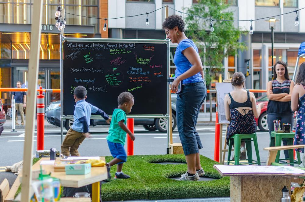 A mother and her kids jump on trampolines at PARK(ing) Day