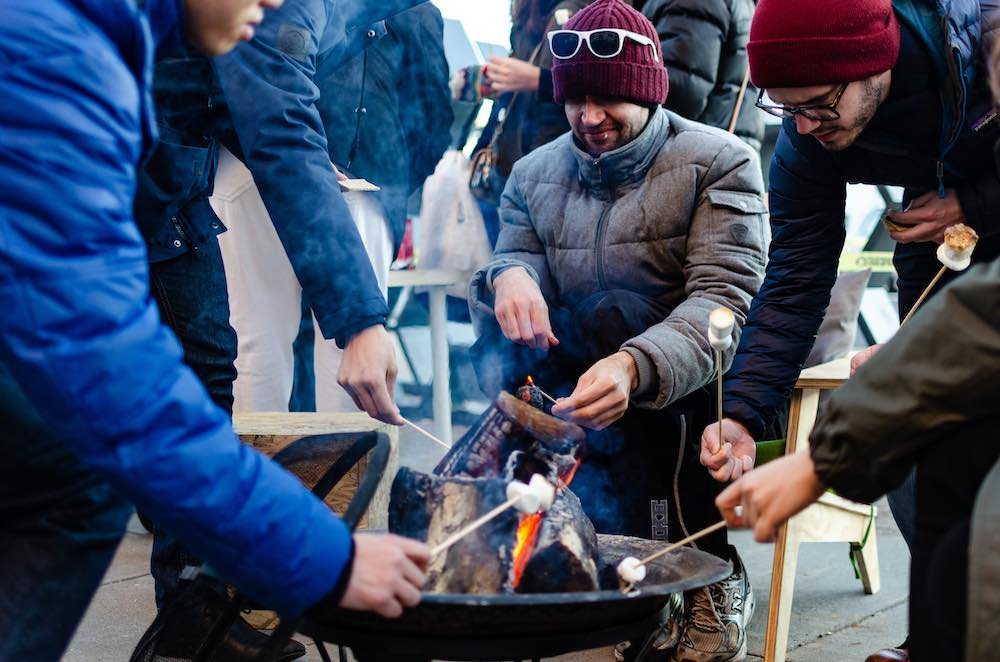 People toast marshmallows around a fire pit in Union Square