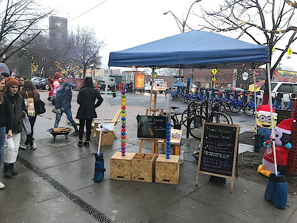 A fire pit, chairs, and tubes with balls in them for voting under a tent at the Union Square Holiday Stroll