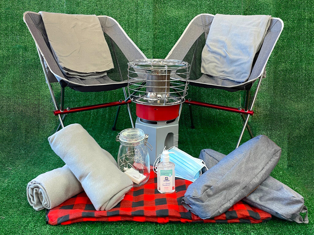 A chair, heater, and light against a green turf backdrop