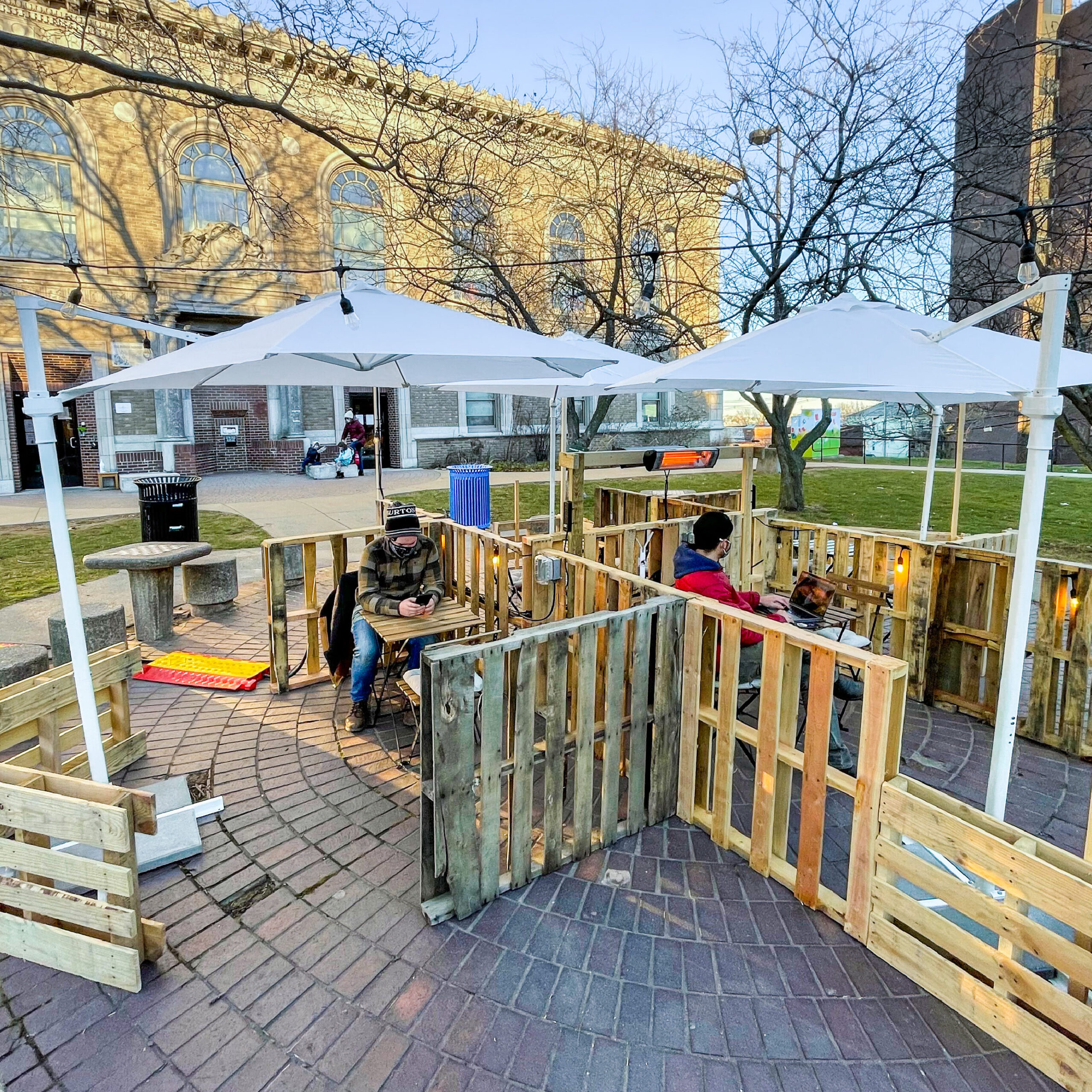 Pallets, umbrellas, and chairs make a outdoor seating area in the courtyard of the Somerville Public Library